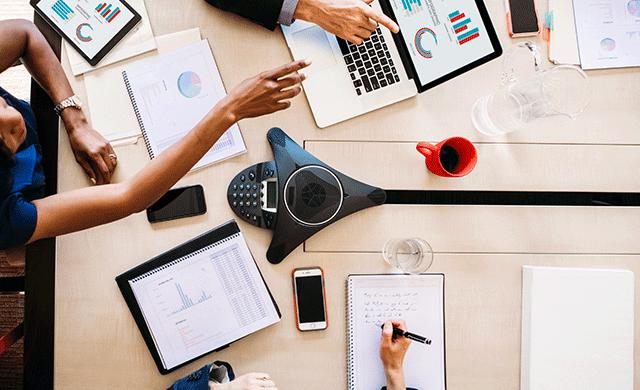 Une vue aérienne d'une table avec un téléphone de conférence, des cahiers, des tasses et d'autres appareils électroniques